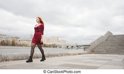 Red-haired girl walking along the promenade. Slow motion