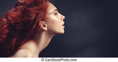 Red-haired girl with flying hair on dark background....