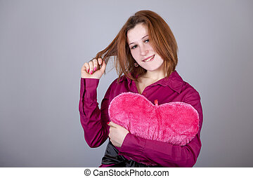 Red-haired girl with heart toy.