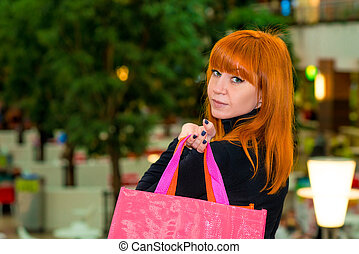 red-haired girl with shopping bags in the mall