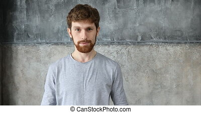 Red-haired guy clapping on a gray wall background -...