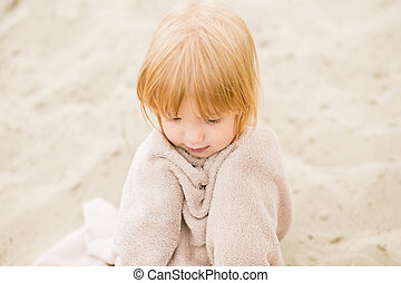 Red-haired little girl in a towel at the beach on hot summer day