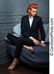 Red-haired man sitting on a couch.