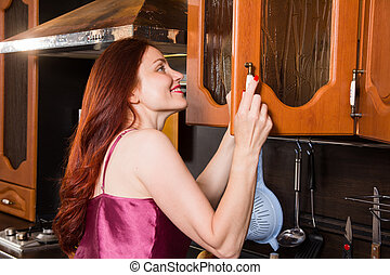 Red-haired middle-aged woman in the kitchen opens the cabinet door
