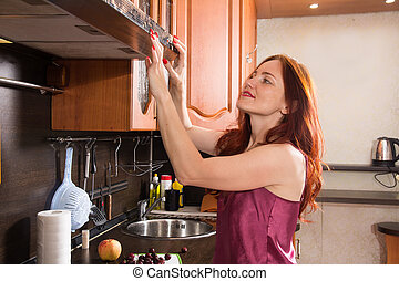 Red-haired middle-aged woman in the kitchen turns off the hood