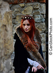 Red-haired princess in a white dress and a black veil with a crown on her head and fur on her shoulders in front of a wall of large stone