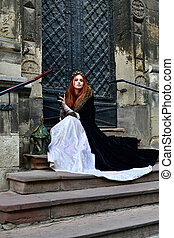 Red-haired princess in a white dress and a black veil with a crown on her head on the stairs with a large iron gate to the temple medieval Lviv