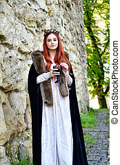 Red-haired princess in a white dress with a crown on her head near the powder tower in medieval Lviv and drinks wine