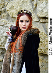 Red-haired princess in a white dress with a crown on her head near the powder tower in medieval Lviv