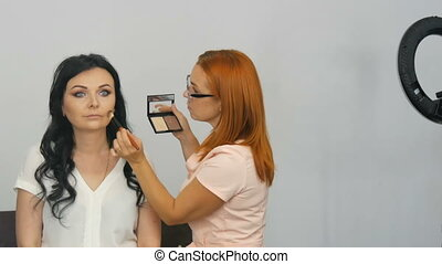 Red-haired stylist make-up artist doing stylish evening...