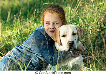 Red-haired teenage girl lying with a dog in the grass.