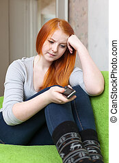 Red-haired teenager girl waits telephone call after quarrel ...