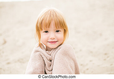 Red-haired toddler girl in towel at the beach on warm summer day