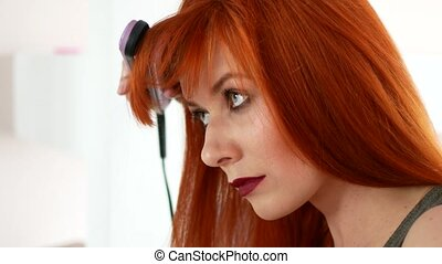 Red-haired woman balancing her hair with an iron before the...
