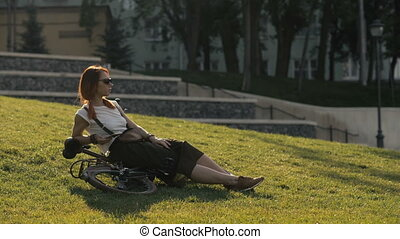 Red haired woman cyclist lying on green grass in city park....