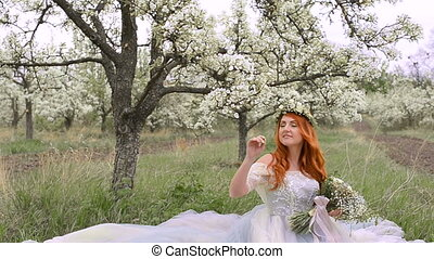 Red-haired woman dressed in a dress sits on the grass in a blooming garden