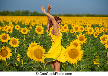 Red-haired woman in a yellow dress dancing with raised hands in a field of sunflowers. Beautiful girl in a skirt sun enjoys a cloudless day in the countryside. Pink locks of hair.