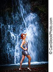 Red-haired woman in front of a waterfall - Portrait of a...