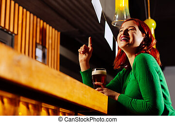 Red-haired woman raising her finger while calling the barman