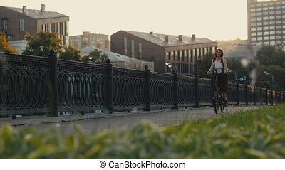 Red haired woman riding bicycle in city on background facade...