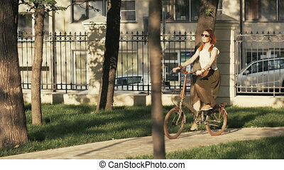 Red haired woman riding bicycle in city park on sunny day