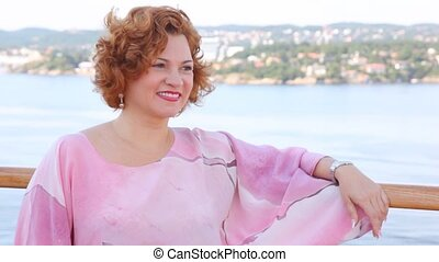 Red-haired woman stands on ship deck in sunny weather