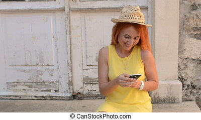 Red-haired woman tourist uses a smartphone on the street of an ancient city