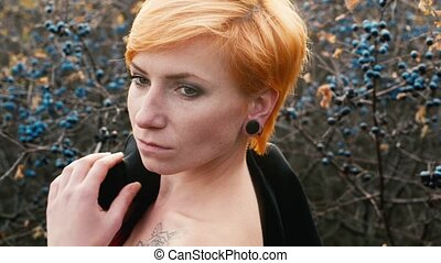 Red-haired woman with bare shoulders posing for a photograph