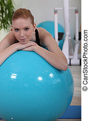 Red-haired woman with blue ball in gym