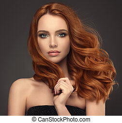 Young red haired woman with voluminous, shiny and wavy hair . Beautiful model with long, dense and curly hairstyle. Flying hair and soft, gentle gesture.
