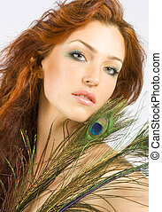 Beautiful red-haired women with peacock feathers in studio shot