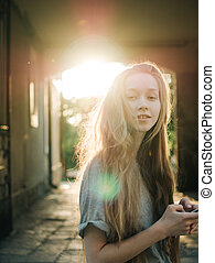 Red-haired young girl in the rays of sunset. City portrait
