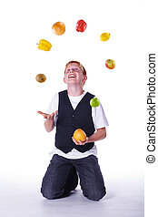 red-haired young juggles fruit