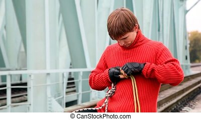 red-haired young man fastens cord standing on railway bridge