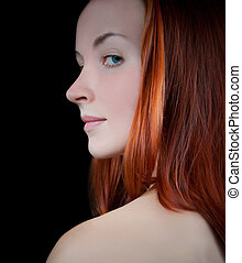 Red haired young woman looking over her shoulder.