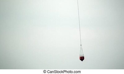 Red hanging scoop from a fire helicopter carries water on...