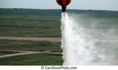 Red hanging scoop from a fire helicopter dumps water on gray...