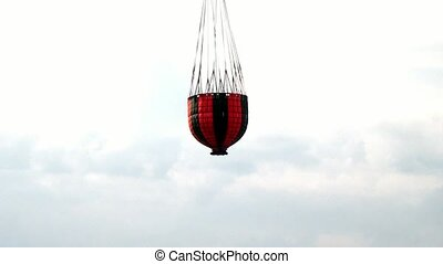Red hanging scoop from a fire helicopter on gray sky...