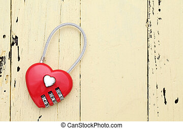 Red hart shaped padlock on wooden background