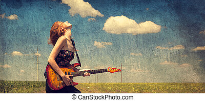 Red-head girl with guitar. Photo in old image style.