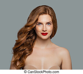 Red head girl with long shiny curly hair. Beautiful model woman with wavy hairstyle