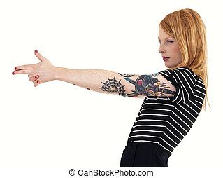 Red head isolated on a white background with arms outstretched and covered in tattoos, pretending to take aim and fire with her hands making the shape of a gun