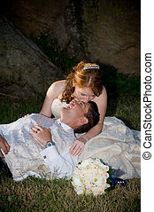 red head sexy beautiful bride in white and groom hugging and sitting outside next to boulders of rocks on green grass