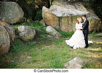 red head sexy beautiful bride in white and groom hugging and standing outside in sun next to boulders of rocks on green grass