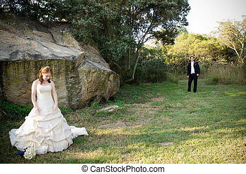red head sexy beautiful bride in white and groom standing outside in sun next to boulders of rocks on green grass