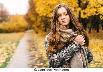 Red-headed freckled girl in autumn yellow park.