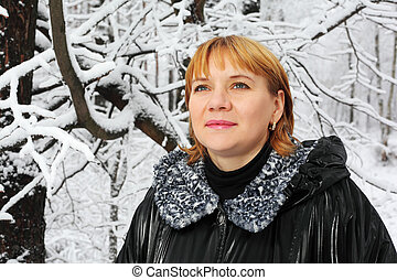Red-headed woman dressed black jacket look up in woods in snow at winter