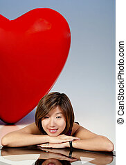 Red Heart - A big red heart behind a beautiful young Asian ...