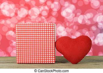 Red heart and Gift Box placed on a wooden floor on a red bokeh background.