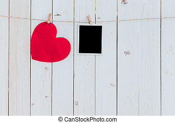Red heart and photo frame blank hanging at clothesline on...